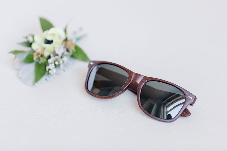 brown grooms sunglasses with boutenierre in background