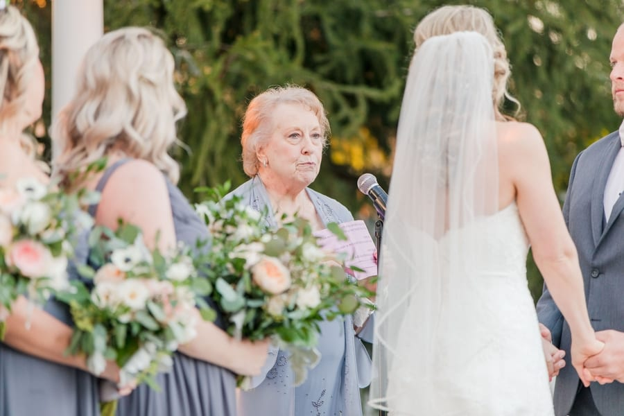 a reading by an older family member during the ceremony with bride and groom on right and bridal party on left