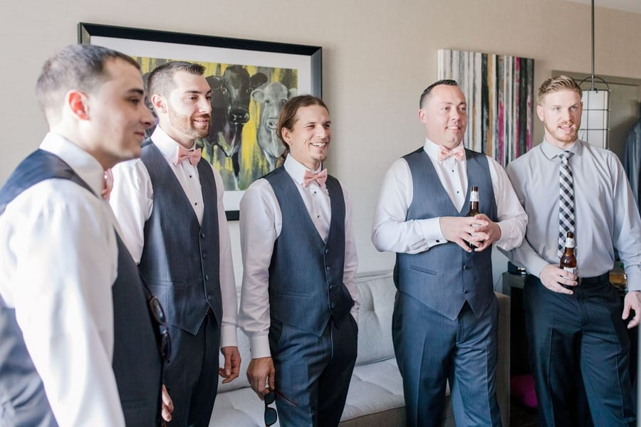 candid of groomsmen enjoying drinks and having laughs