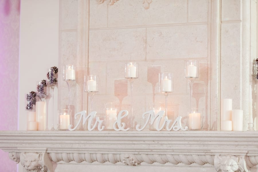 fireplace mantle decorated with Mr and Mrs sign and candles