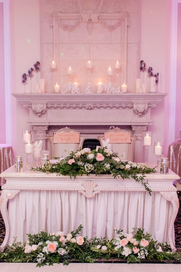 sweetheart table with greenery in front of fireplace mantle