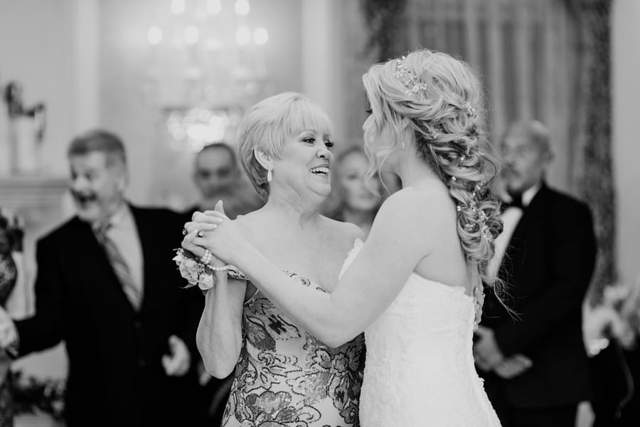 close up black and white photo of bride dancing with her mother