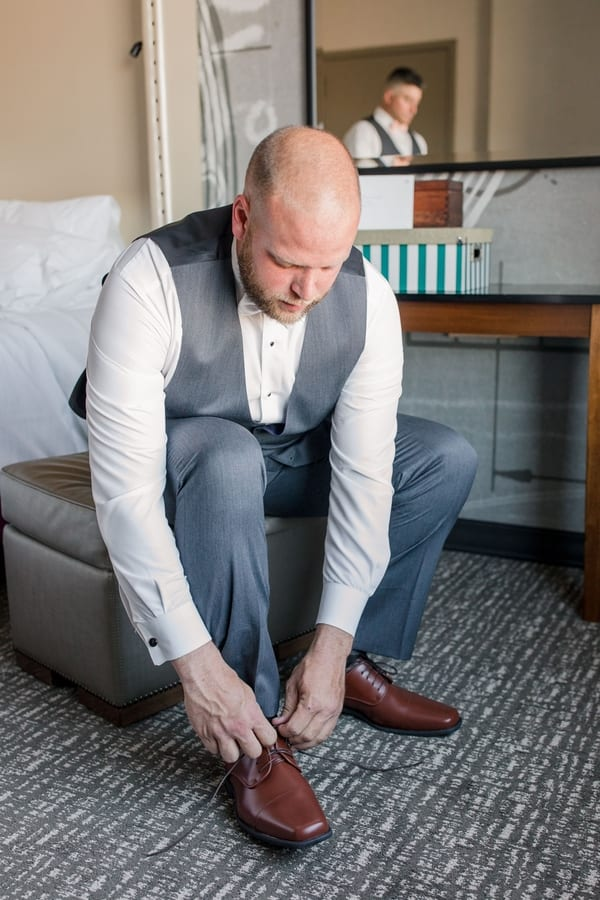 groom tieing the shoelace of his brown shoe