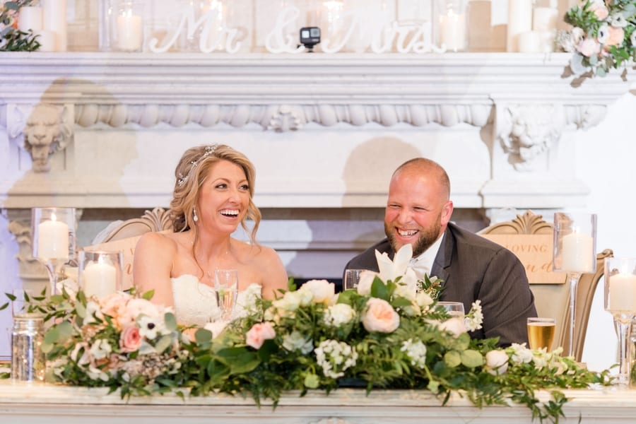 bride and groom laughing while sitting at the sweetheart table