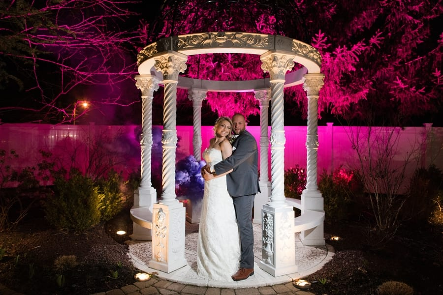 bride and groom outside in a stone gazebo at the Primavera Regency with pink uplighting in the background