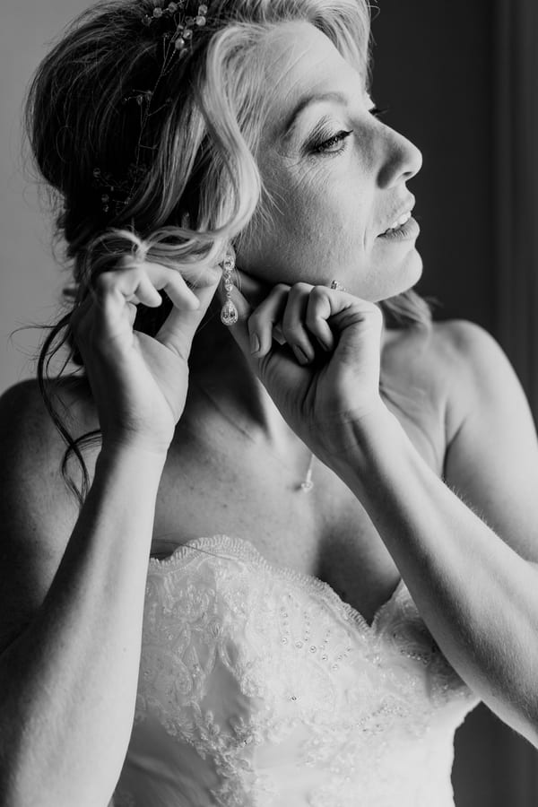black and white photo of bride putting in her earring