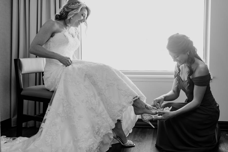 black and white photo of bridesmaid assisting bride with her shoes
