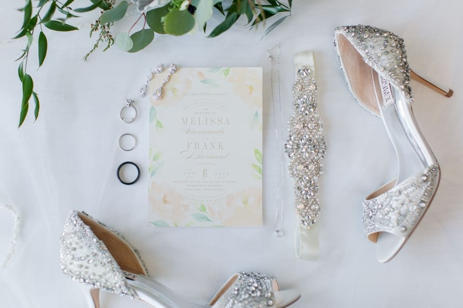 brides shoes and accesories displayed around the wedding invitation and jewelery