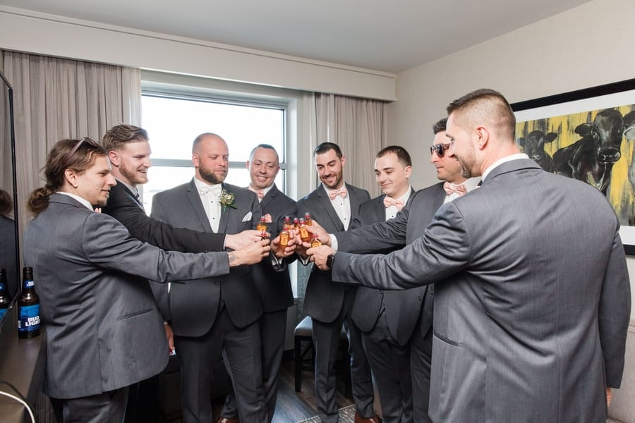 groom and groomsmen cheersing their Fireball liquor shots before drinking them