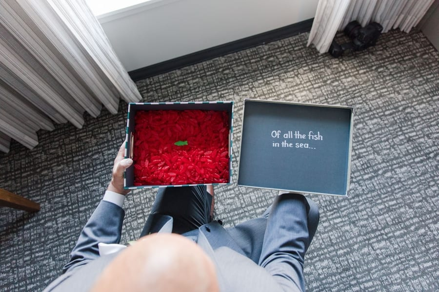 """overhead shot of groom holding a gift box full of red swedish fish with one green fish """"of all the fish in the sea"""""""