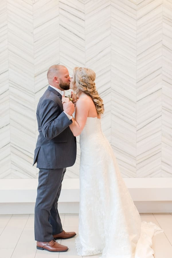 full length photo of ride and groom embracing, holding hands and kissing in front of white patterned wall
