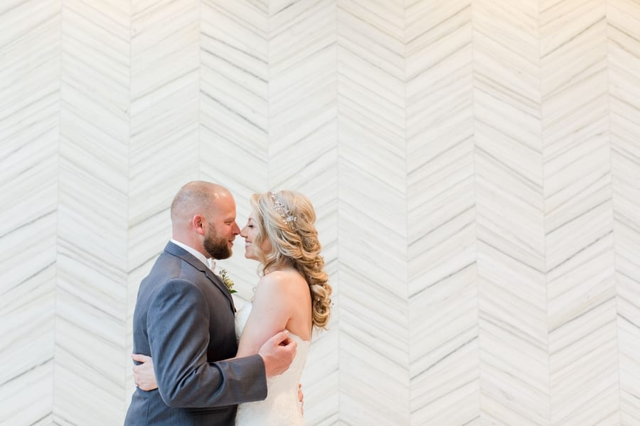 bride and groom embracing with noses together in front of white patterned wall