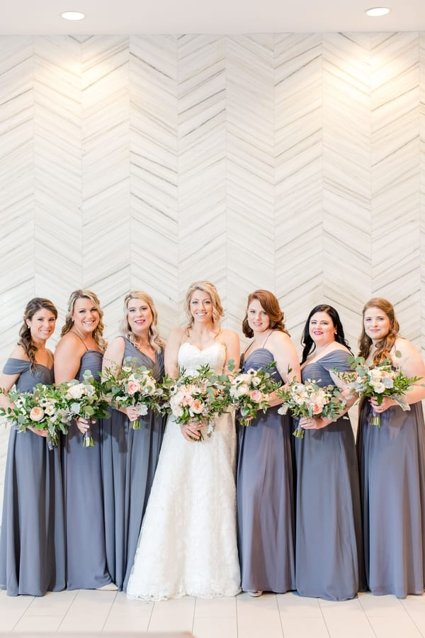 full length photo of bride and bridal party in grey gowns in formal photo