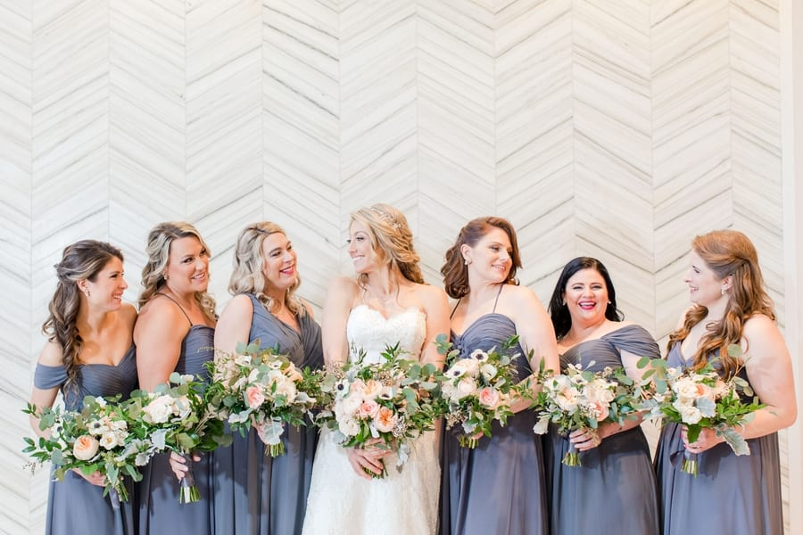 wide angle photo of bride and bridal party in grey gowns in a casual photo