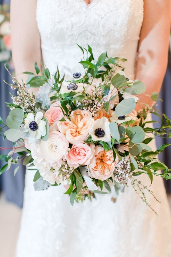 close up shot of bride holding bridal bouquet of greens and peach and ivory florals