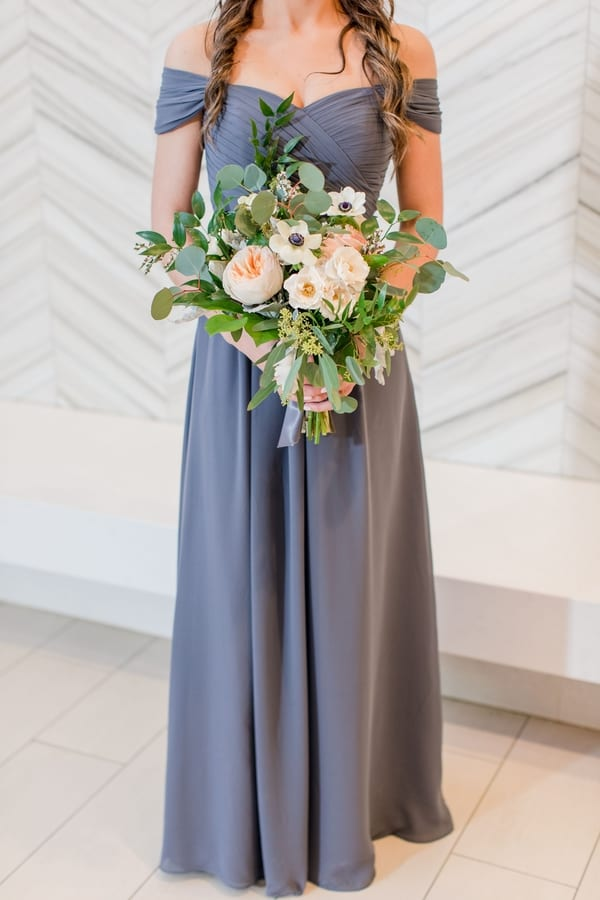 3/4 shot of bridesmaid in grey gown holding bridesmaid bouquet of greens and peach flowers