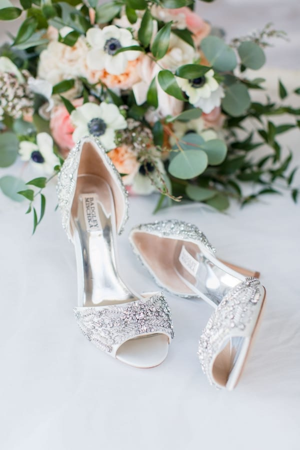 brides crystal covered heels positioned in front of brides bouquet of greenery and peach colored flowers