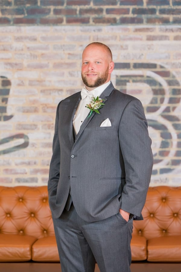 portrait of groom in lobby of Embassy Suites Berkely Heights standing in front of painted brick wall and cognac colored leather couch