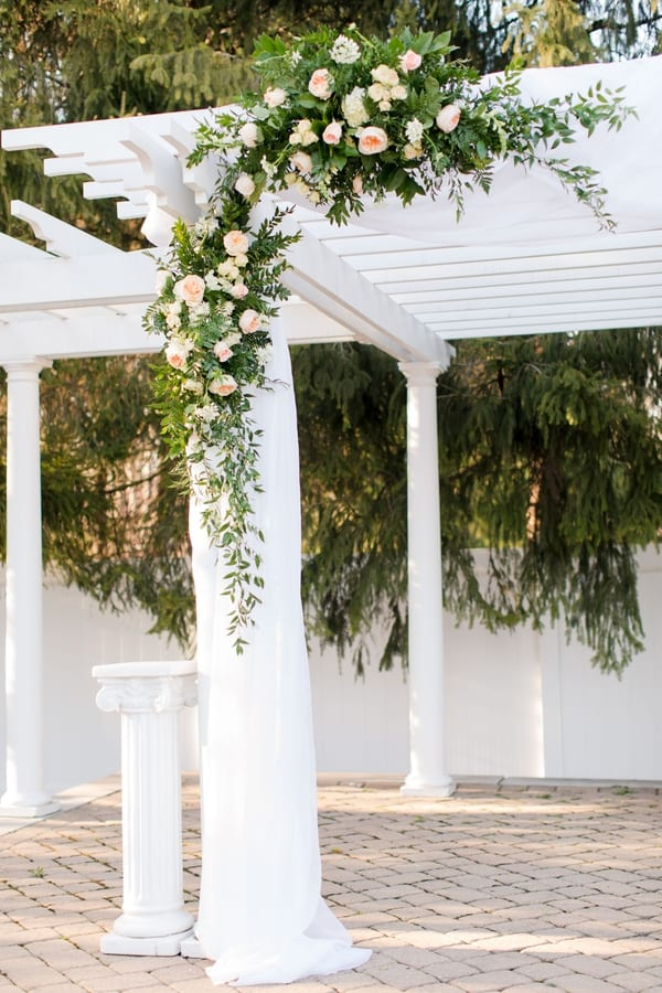 ceremony pergola details of greenery and peach florals