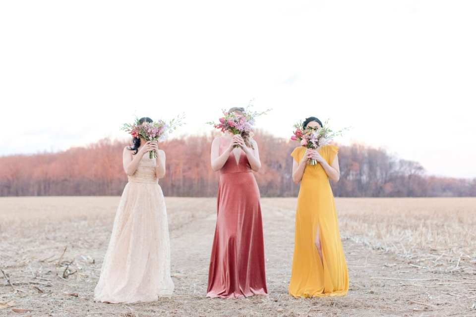 three bridesmaids in different colored, yet coordinating, gowns standing outside holding hand tied bouquets of spring and wildflowers in front of their faces