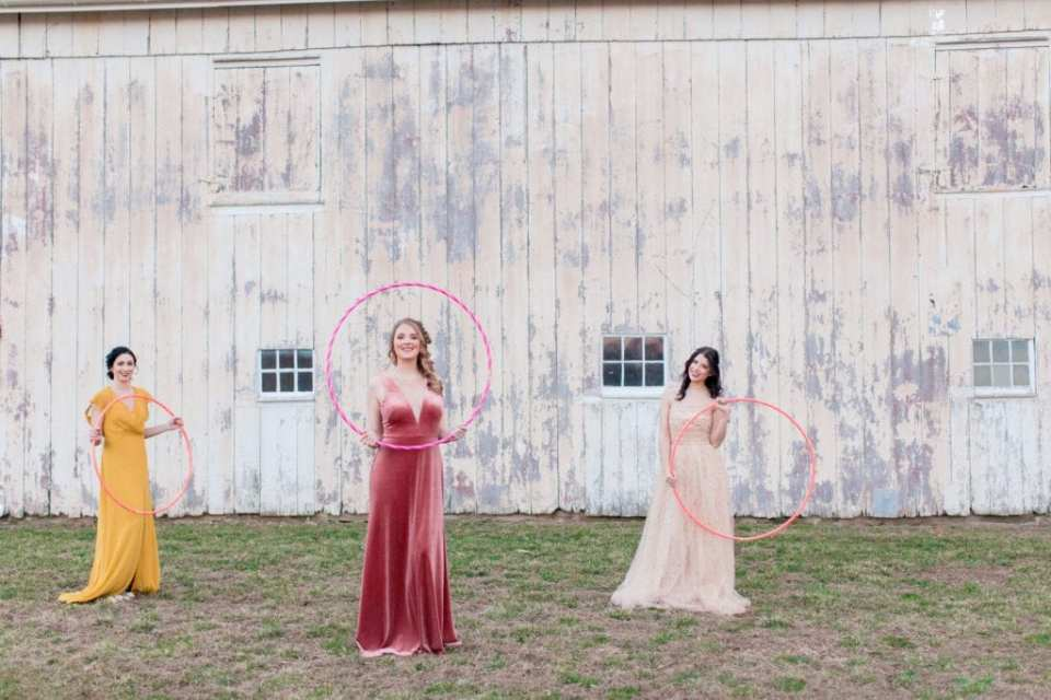 three bridesmaids in different colored, yet coordinating, gowns standing outside a rustic whitewashed barn holding hula hoops playfully