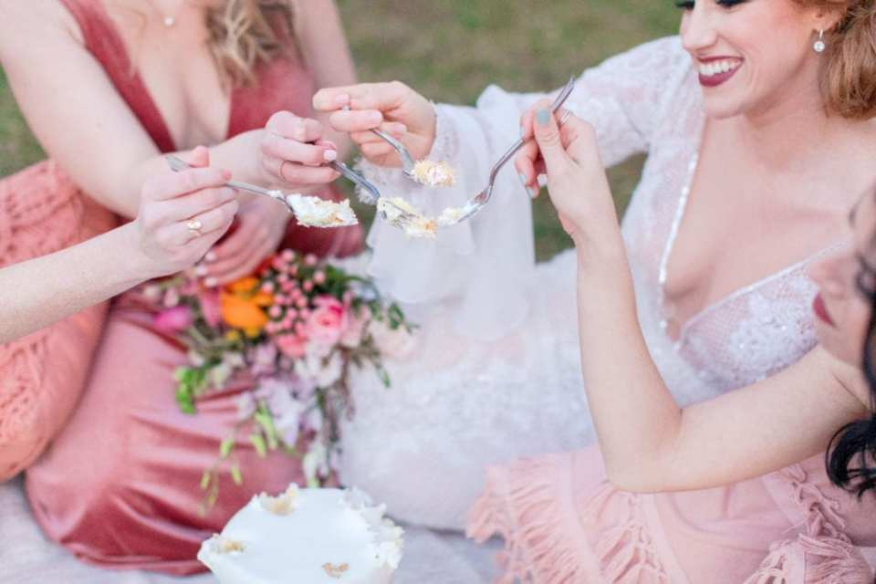 bohemian bride and her bridesmaids picnicking on cake