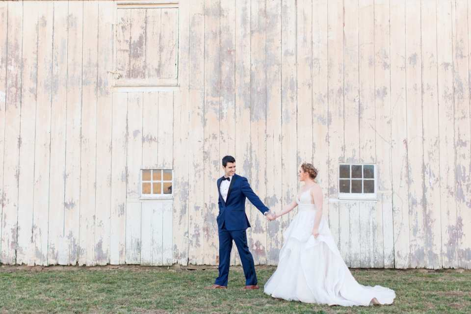 bride in spaghetti strap floral lace with crown of flowers in hair with her groom in a navy blue and black tuxedo walking through the property at Updike Farmstead in Princeton New Jersey