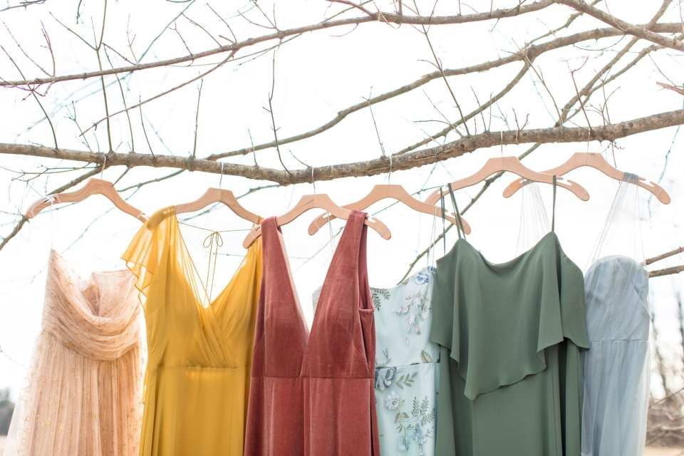multicolored bridesmaid gowns handing on wooden hangers from a branch outside