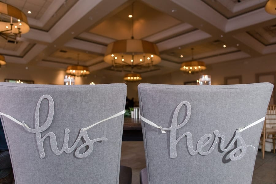 "photo of the bride and grooms chairs at the sweetheart table labelled with ""his and hers"" silver glitter hanging signage"