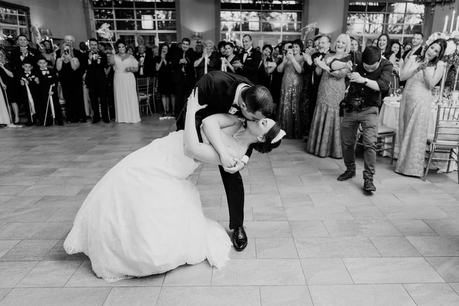 black and white photo of groom dipping bride at the end of their first dance