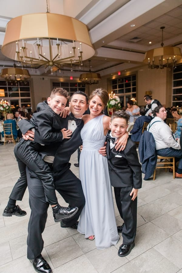a family of four guests, including two young boys, pose for fun family photo during the reception