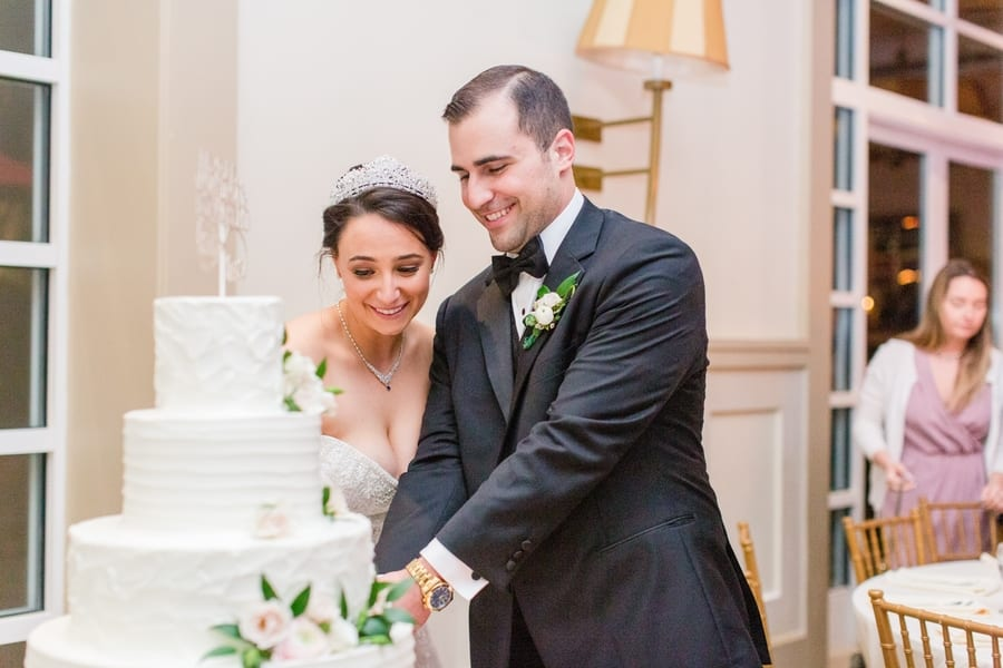 bride and groom smiling while cutting the cake