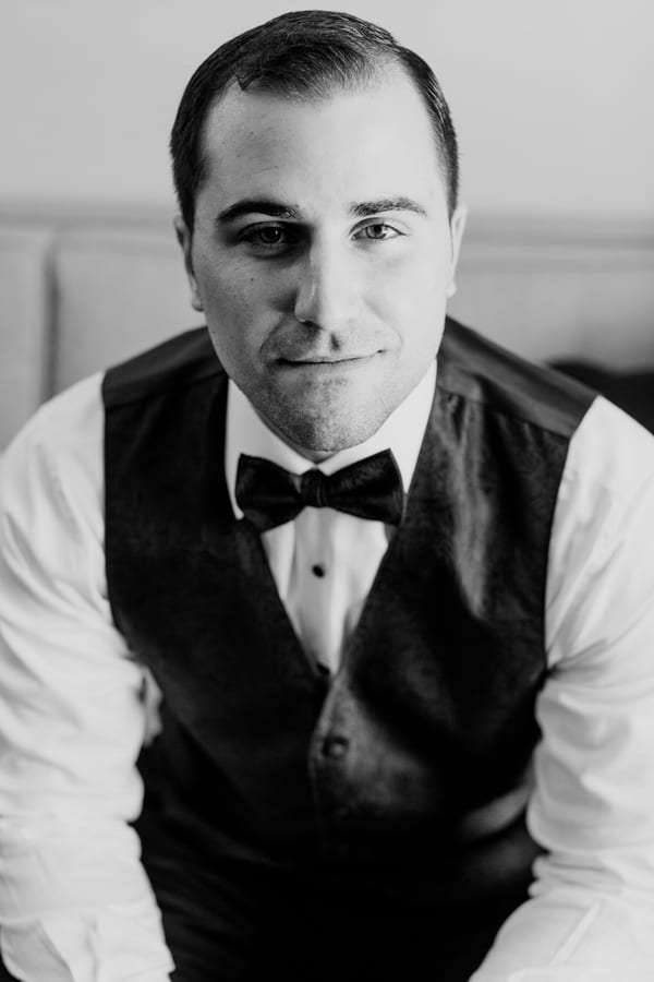 black and white photo of groom in tuxedo vest and bow tie