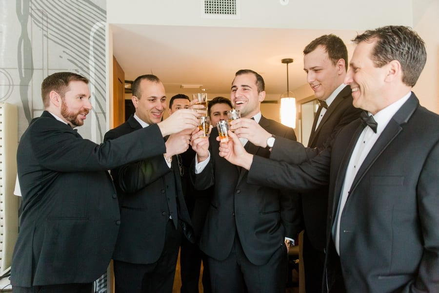 groom and his groomsmen enjoying shots while getting ready