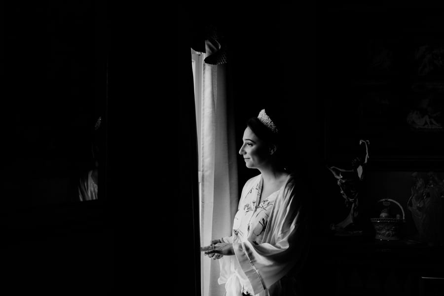 black and white photo of bride in her prep outfit gazing out the window