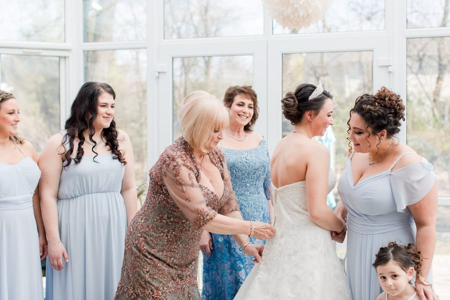 bride being helped into her gown by her bridal party in powder blue gowns and her mother in a copper gown