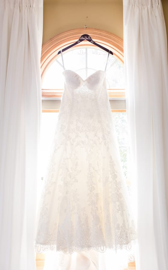 brides gown hanging on a personalized hanger against a window framed by white drapes