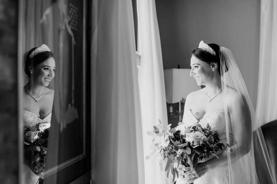 black and white photo of bride looking out the window, with her reflection appearing in a mirror on the left side of the photo