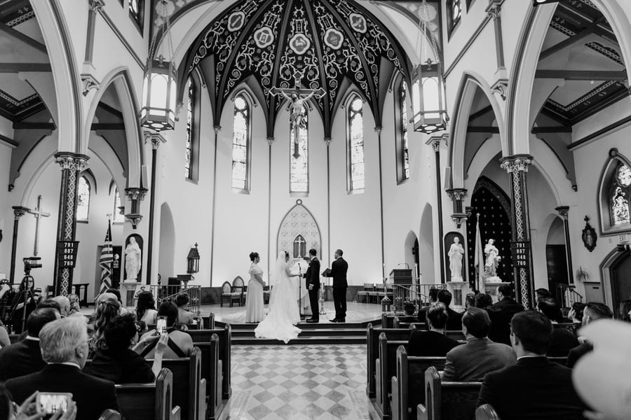 black and white photo of the bride and groom holding hands at the altar of the church
