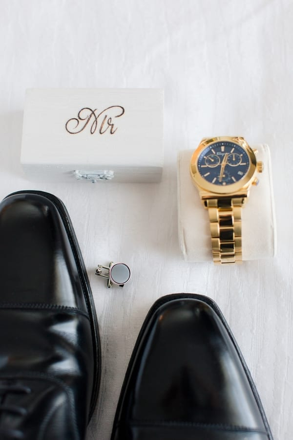 detail photo of grooms gold watch, grey cufflink, black shoes and white wooden box with a gold Mr on it