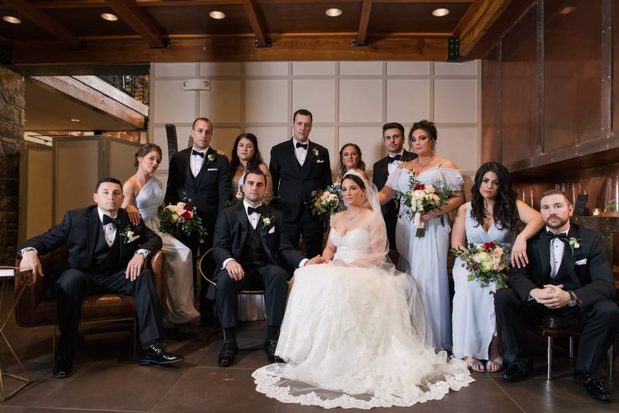 formal photo of wedding party posed around the bride and groom seated in the center