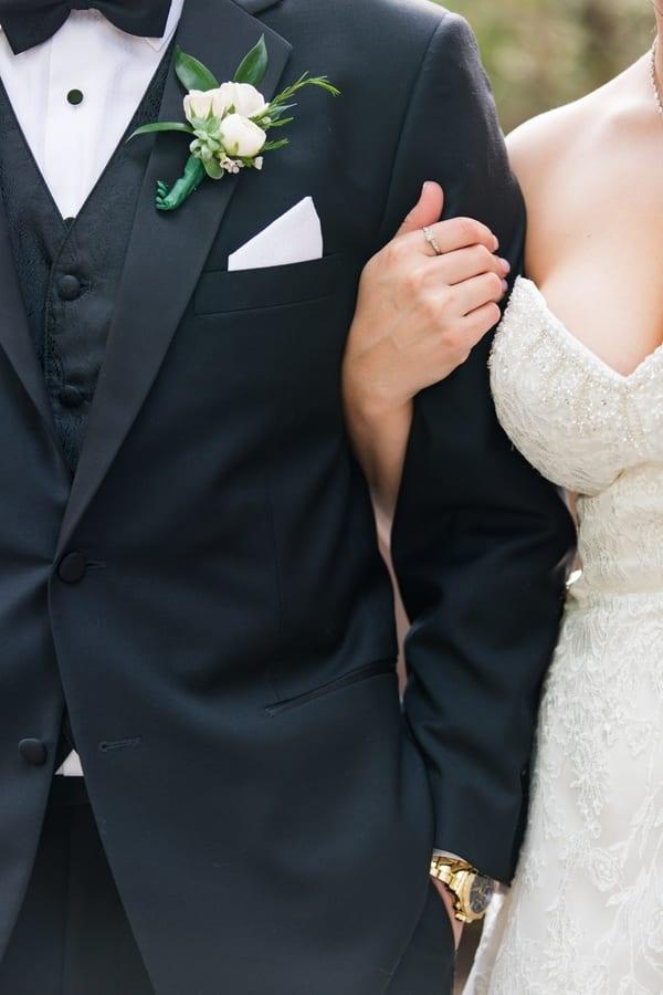 close up of brides right hand around her grooms arm, no faces in photo