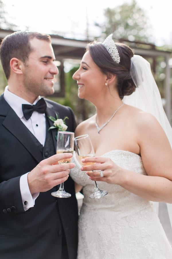bride and groom smiling at each other outdoors while toasting with champagne flutes