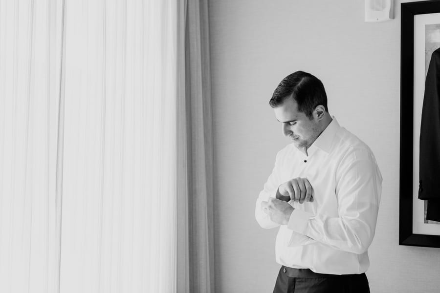 black and white photo of groom putting on his cuff links