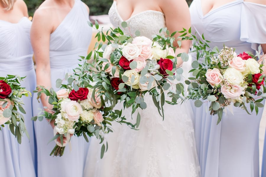 close up of the bride and bridesmaids bouquets of blush, cream and red florals