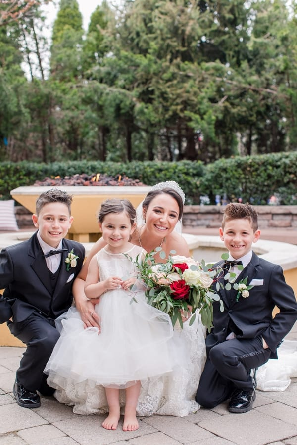 bride on ground in front of fire pit with two ring bearers and flower girl (who is wearing no shoes)