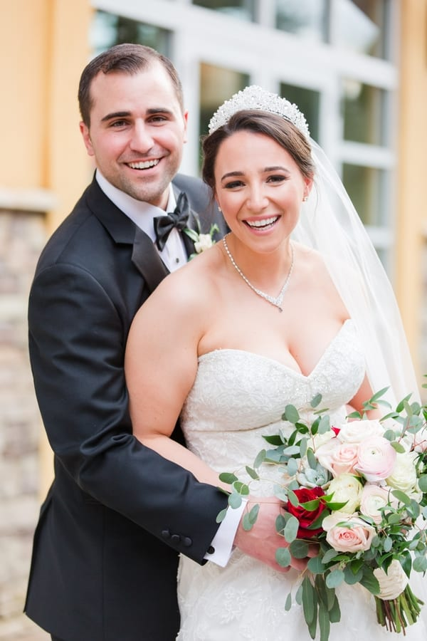 portrait of bride and groom smiling while she holds her bouquet, all in front of the Stone House