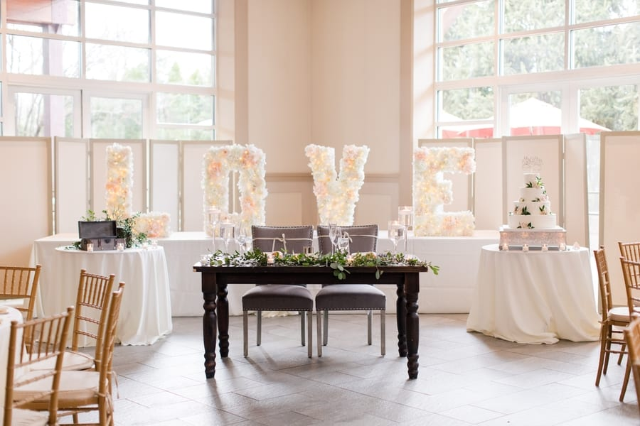 wide angle shot of wooden sweetheart table with greenery, two grey chairs, cake displayed on one side of the table, the wine box card holder on the opposite side, with large love floral arrangement behind the table