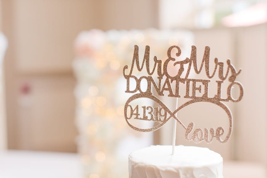 close up of personalized glitter cake topper with bride and grooms married name and the date of their wedding