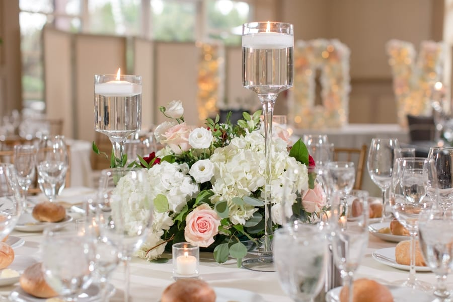 low reception floral arrangement of white hydrangea and roses in blush pink, red, white surrounded by floating candles in individual candle holders